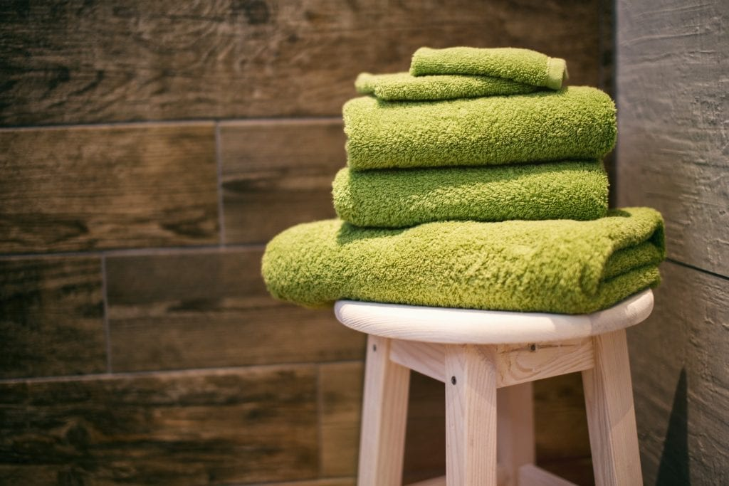 green towels on.a wooden chair in a custom new home bathroom